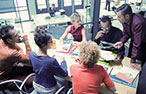 A group of 5 adult learners discuss their work at a meeting table with an instructor.
