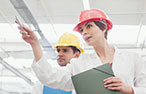 A team of three people wearing lab coats and hard hats inspect a factory