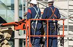 Two male workers wear a safety harness on a harness platform.