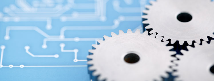 Three aligned gears lie on top of a page of design plans.