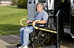 A man in a wheelchair is lifted into a wheelchair accessible van.