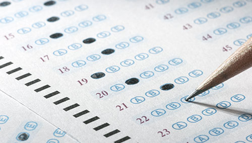 A man completes a multiple choice exam questionnaire.