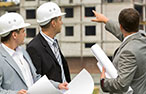 Three construction workers wearing suits and carrying plans stand outside a construction site.